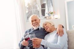 Couples supérieurs heureux caressant tout en buvant l'épouse Photo libre de droits
