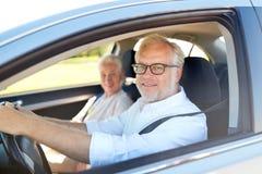 Couples supérieurs heureux conduisant dans la voiture Photo stock