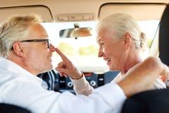 Couples supérieurs heureux conduisant dans la voiture Image stock