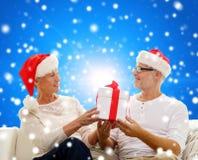 Couples supérieurs heureux dans des chapeaux de Santa avec le boîte-cadeau Images libres de droits
