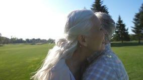 Couples supérieurs heureux dans l'amour étreignant sur la pelouse verte banque de vidéos