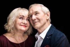 Couples supérieurs heureux dans l'amour se tenant ensemble sur le noir Images stock