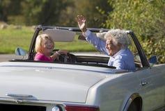 Couples supérieurs heureux dans la voiture de sport de vintage Image stock