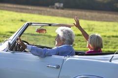 Couples supérieurs heureux dans la voiture de sport de vintage Photo stock