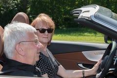 Couples supérieurs heureux de sourire dans la voiture de sport Photos stock