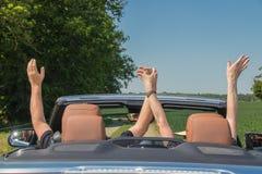 Couples supérieurs heureux de sourire dans une voiture convertible de luxe Image libre de droits