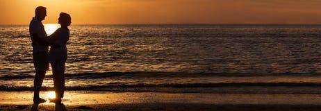 Couples supérieurs heureux embrassant sur le panorama de plage de coucher du soleil photographie stock
