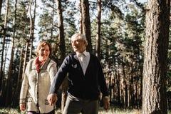 Couples supérieurs heureux marchant en parc photo stock