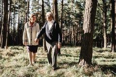 Couples supérieurs heureux marchant en parc image stock