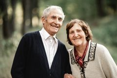 Couples supérieurs heureux marchant en parc photos stock
