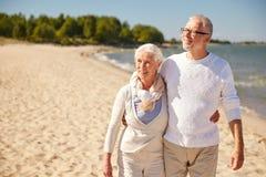Couples supérieurs heureux marchant le long de la plage d'été Photo libre de droits