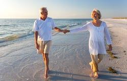 Couples supérieurs heureux marchant retenant la plage tropicale de mains images stock