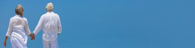 Couples supérieurs heureux marchant tenant le panorama de ciel bleu de mains photo stock