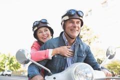 Couples supérieurs heureux montant un vélomoteur Image stock