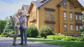 Couples supérieurs heureux montrant des clés à la nouvelle grande maison banque de vidéos
