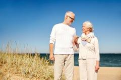 Couples supérieurs heureux parlant sur la plage d'été Photos stock