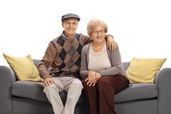 Couples supérieurs heureux posant ensemble sur un sofa Photo libre de droits