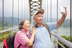 Couples supérieurs heureux prenant la photo avec le selfie futé de téléphone Photographie stock