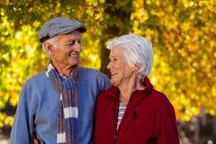 Couples supérieurs heureux regardant l'un l'autre en parc pendant l'automne Image libre de droits