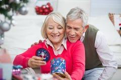 Couples supérieurs heureux regardant le cadeau de Noël Images libres de droits