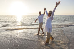 Couples supérieurs heureux retenant la plage de lever de soleil de coucher du soleil de mains Image stock