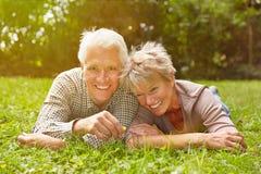 Couples supérieurs heureux s'étendant dans le pré Images stock