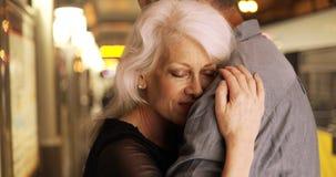 Couples supérieurs heureux s'embrassant à la station de train Photographie stock
