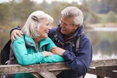 Couples supérieurs heureux se penchant sur une barrière en bois souriant entre eux, fin, secteur de lac, R-U photographie stock