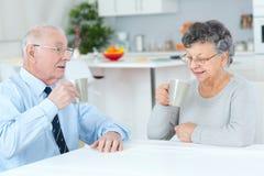 Couples supérieurs heureux se reposant à la table et au café potable Image libre de droits