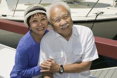 Couples supérieurs heureux se reposant dans le bateau Photographie stock