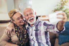 Couples supérieurs heureux se reposant ensemble sur un sofa dans leur salon Photographie stock