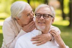 Couples supérieurs heureux se reposant sur le banc au parc Image libre de droits