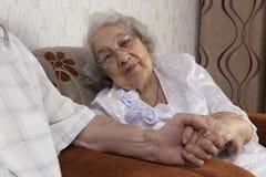 Couples supérieurs heureux se reposant sur le sofa image stock