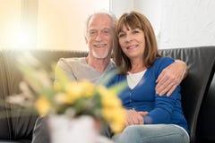 Couples supérieurs heureux se reposant sur le sofa et s'embrassant, effet de la lumière Images stock