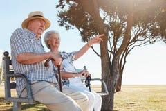 Couples supérieurs heureux se reposant sur un banc de parc Image libre de droits