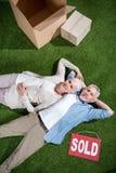 Couples supérieurs heureux se trouvant sur l'herbe verte entre les boîtes en carton et le signe vendu Photographie stock