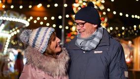 Couples supérieurs heureux souriant au marché de Noël banque de vidéos