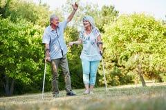 Couples supérieurs heureux sur des béquilles en parc Photos stock