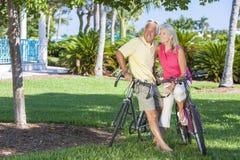 Couples supérieurs heureux sur des bicyclettes en stationnement vert Photos libres de droits