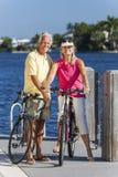 Couples supérieurs heureux sur des bicyclettes par une rivière Photographie stock