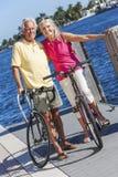Couples supérieurs heureux sur des bicyclettes par une rivière Images libres de droits