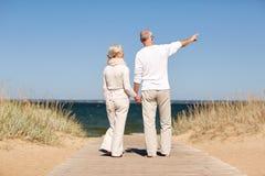 Couples supérieurs heureux sur la plage d'été Image stock