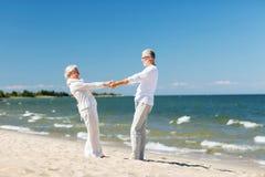 Couples supérieurs heureux tenant des mains sur la plage d'été Images stock