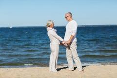 Couples supérieurs heureux tenant des mains sur la plage d'été Photo libre de droits