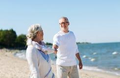 Couples supérieurs heureux tenant des mains sur la plage d'été Photo stock