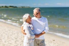 Couples supérieurs heureux tenant des mains sur la plage d'été Photographie stock libre de droits