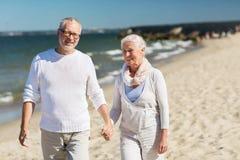 Couples supérieurs heureux tenant des mains sur la plage d'été Image libre de droits