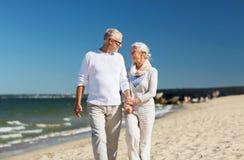 Couples supérieurs heureux tenant des mains sur la plage d'été Photographie stock