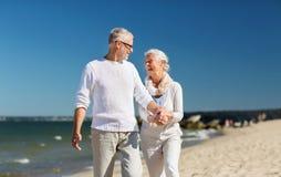 Couples supérieurs heureux tenant des mains sur la plage d'été Image stock