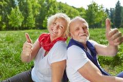Couples supérieurs heureux tenant des pouces  Photos stock